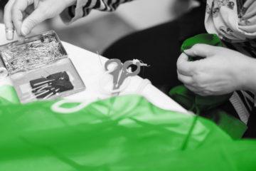 Lähikuva ompelijan käsistä, työvälineistä ja vihreästä kankaasta.
